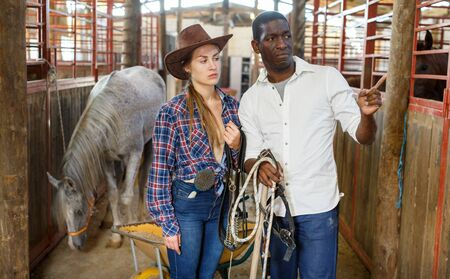 Farm workers man and woman talking emotionally standing at stable