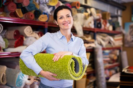 Smiling female keep in hand colored carpet in interior shop Stockfoto
