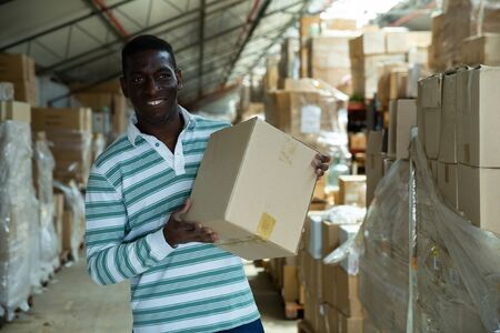 African-American man working in wholesale warehouse, placing cartons with goods Stock Photo