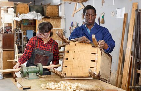 Portrait of male and female restorers working with wooden furniture in workshop