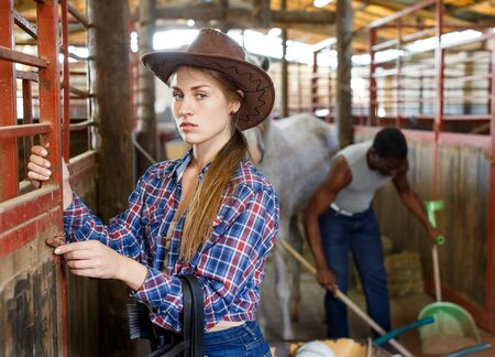 Portrait of girl farm worker standing at horse stable