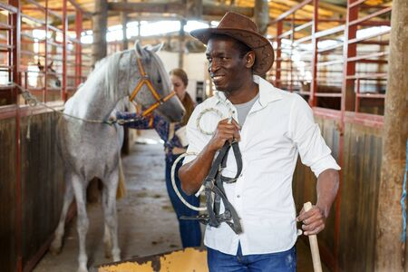 Portrait of mature afro man farm worker standing at horse stable