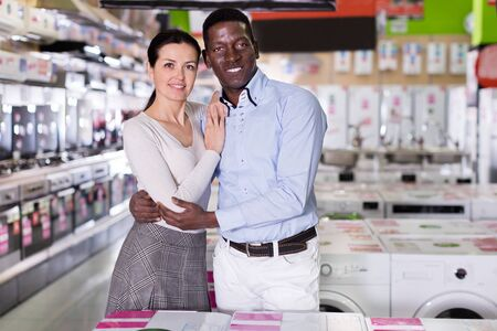 Positive couple standing in a store of the household appliances. Focus on both persons