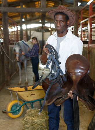 Couple of farmers man and girl harnessing horse in stable