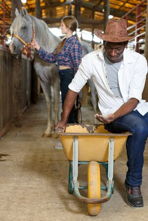 Portrait of positive couple man and woman near wheelbarrow with corn in stable