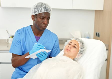 Man cosmetologist examining patient and writing documents before beauty procedure in clinic of esthetic cosmetology 写真素材