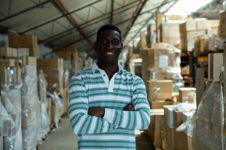 Portrait of successful African American warehouse manager standing with arms crossed against boxes of goods Stock Photo