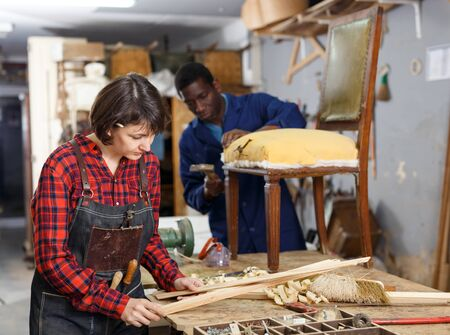 Portrait of male and female artisans in process of renewing vintage armchair in workshop