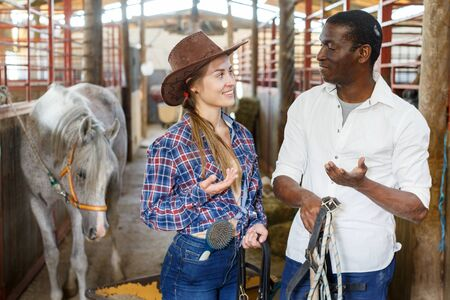 Portrait of couple of horse farm workers cheerful man and woman at stable
