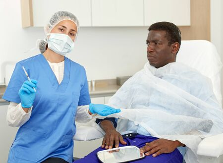 Cosmetician female preparing to aesthetic facial injection with man in medical  office