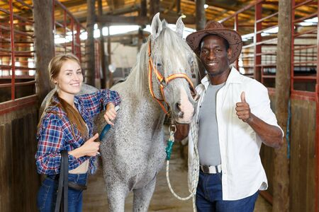 Happy afro man and European girl in working clothes posing near gray horse at horse stable