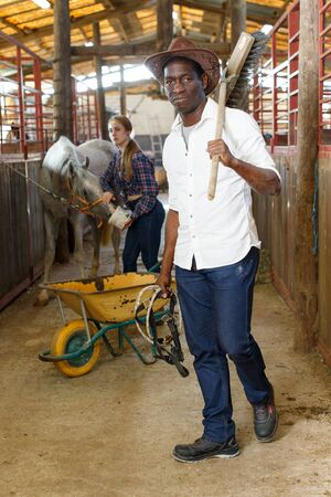 Cheerful mature african man in working clothes posing at stable