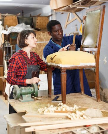Woman and man carpenters inspecting old wooden chair in studio