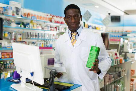 Portrait d'un pharmacien mâle joyeux et expérimenté, conseillant sur les médicaments en pharmacie