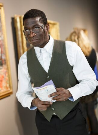 Positive Afro-American man with booklet standing at hall of museum and looking at painting