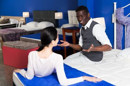 Positive multinational couple is choosing new furniture for bedroom in the store