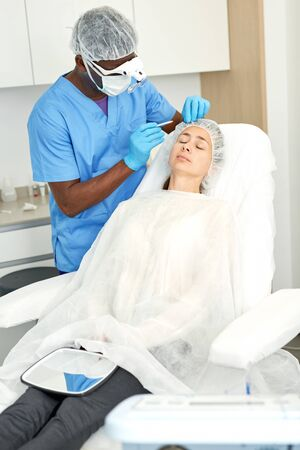 Cosmetologist man in mask preparing  woman client for mesotherapy  procedure  in medical  office 写真素材