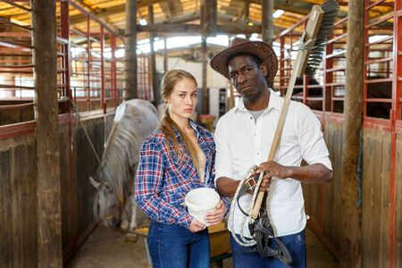 Portrait of smiling adult man and young woman workers of horse stable