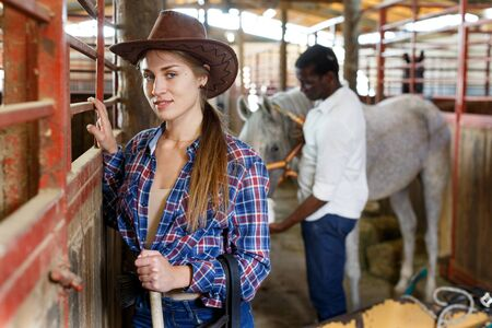 Attractive young woman who works at stable Stock Photo