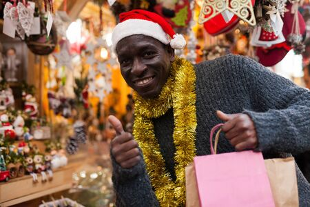 Portrait of smiling African American man in Santa hat with shopping bags on festive fair before Christmas