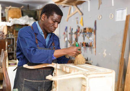 Restaurateur professionnel de meubles renouvelant la commode vintage en atelier