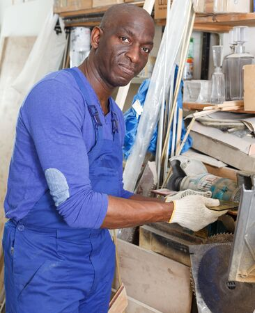 Confident African American glazier working on glass edge polishing machine in glass workshop