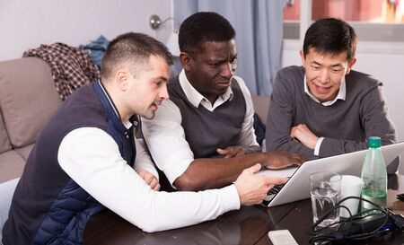 Cheerful male friends using laptop during bachelor gathering at home Stock fotó