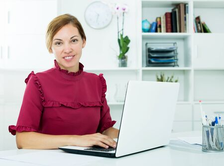 Cheerful young woman sitting at office and working with laptop indoors