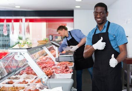 Happy  smiling African American seller of butcher store standing behind counter, giving thumbs up