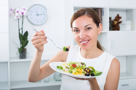 Cheerful young woman enjoying fresh crunchy salad indoors