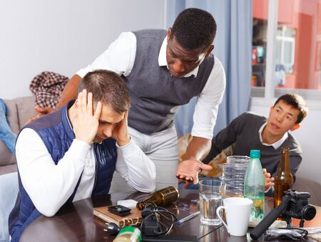 Upset man dont speaking with two friends during quarrel indoors Stock Photo