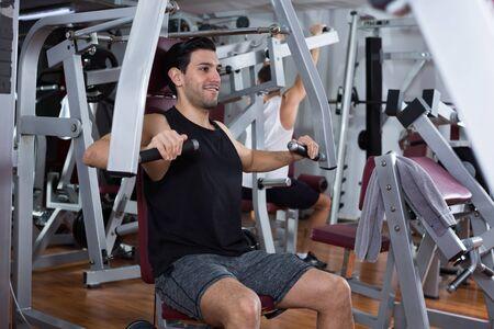 Muskulöser Mann, der Krafttraining auf Fitnessmaschine im modernen Fitnessstudio tut