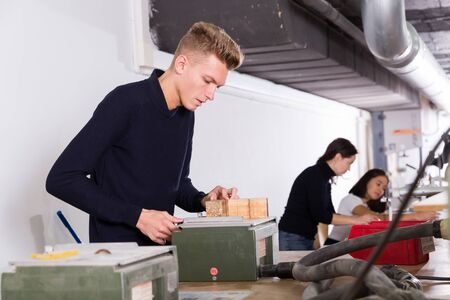 Student of faculty of architecture engaged in architectural modeling in university studio Stock Photo