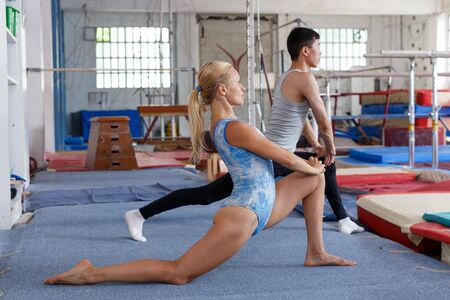 Man and woman doing acrobatic exercises on floor of gym