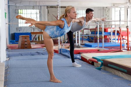 Positive mature woman and man gymnasts exercising gymnastic action at gym