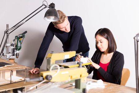 Young teacher helping girl making elements on scroll saw for architectural model in university workshop