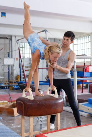 Fit man and woman doing acrobatic exercises on pommel horse in the gym securing each other Foto de archivo - 128252929