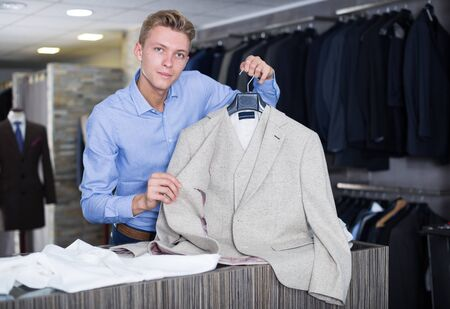 Adult male in shirt selling business clothes jacket in the store Banco de Imagens