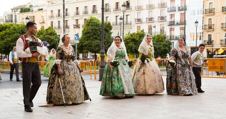 VALENCIA, SPAIN - MARCH 18, 2019: Adult people and children participating in costumed procession on traditional spring festival Fallas Sajtókép