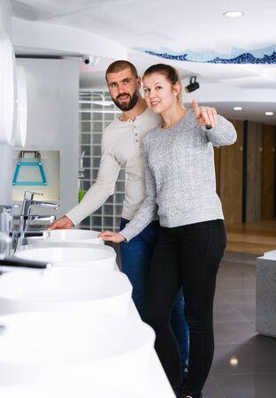 Positive couple choosing wash basin in bathroom furniture shop 写真素材