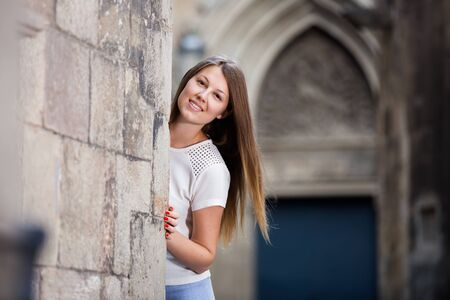 Young smiling woman looking out from behind old stone wall during walk