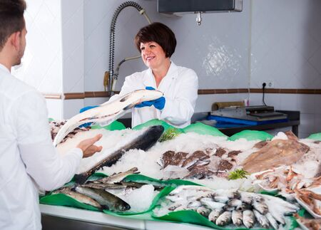 Positive woman selling chilled fish and seafood in store