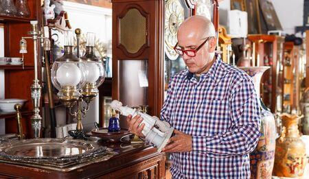 Interested adult man collector of vintage goods choosing ancient things in antique shop