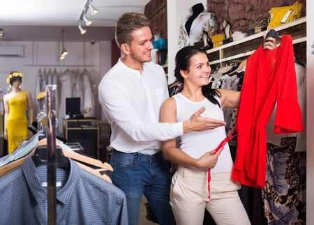 portret of young couple buying red jacket and dress at boutique
