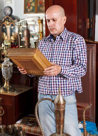 Uomo di mezza età intelligente che sceglie per l'artigianato retrò nel negozio di antiquariato Archivio Fotografico