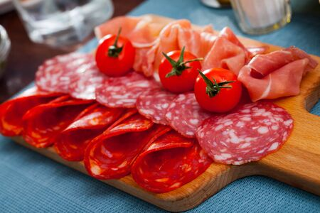 Appetizing cold cuts from Spanish ham and spicy dry-cured sausages with cherry tomatoes on wooden board Stock Photo