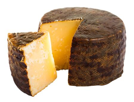 Spanish cheese queso manchego from milk of sheep with cut piece. Isolated over white background