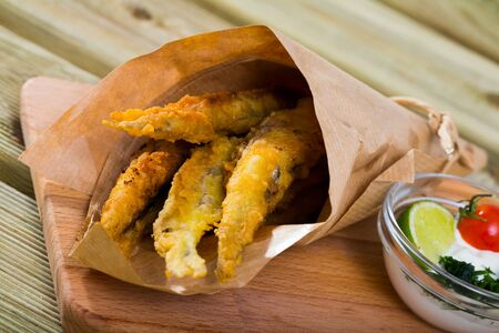 Traditional Spanish tapas - deep fried anchovies served with creamy cheese sauce, lime and greens