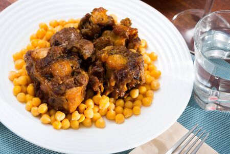 Braised oxtails with chickpeas on a white plate Stock Photo