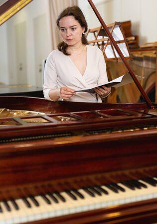 Hübscher Frauenverkäufer im Klaviermusikladen